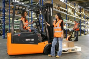 Team members pose alongside a Doosan reach truck